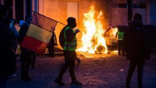 Протестувальник з прапором Франції біля палаючої машини