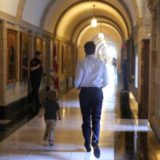 Photographed from behind, Justin Trudeau and his three-year-old son run down an expensive-looking government building while smiling security guards look on