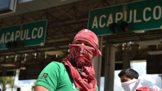 Hombre encapuchado delante de un cartel de Acapulco.
