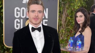 Model stands and poses in background of shot with actor Richard Madden