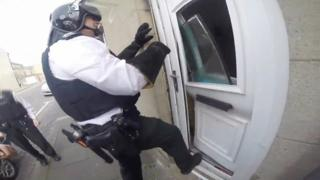 A police officer kicks in a door of a house