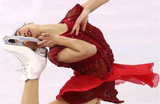 Kaori Sakamoto holds her ice skate up to her head whilst competing