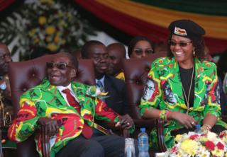 Zimbabwean President Robert Mugabe (L) and his wife Grace (R) smile after arriving at the Rudhaka Stadium in Marondera, about 100 kilometers east of Harare