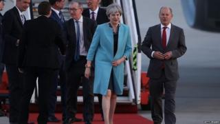 Theresa May greeted by Olaf Scholz, the mayor of Hamburg, as she arrives in the city for the G20 summit