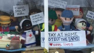 "Knitted figures in window with signs ""Stay at home. Protect the NHS"" and ""We stayed at work for you now stay at home for us please"""