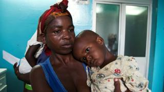 A mother holds her child suffering from yellow fever at a hospital in Luanda, Angola, March 15, 2016
