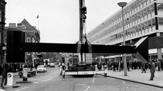 A black and white photograph of the sculpture being lifted by a crane