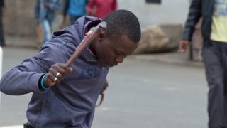 Man holding monkey wrench over Manuel Sithole