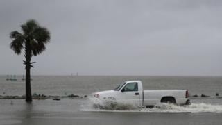 A driver navigates along a flooded road as the outer bands of Hurricane Sally come ashore on September 15, 2020 in Bayou La Batre, Alabama