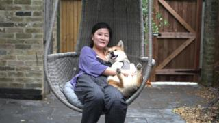 Meena holds Gus a rescue dog from a South Korean dog meat farm.