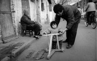 A young girl walks with her grandma in the street