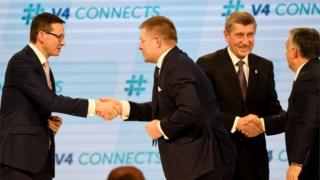 Members of the Visegrad group shake hands on stage