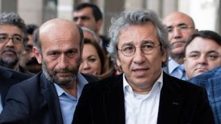 イスタンブールの裁判所前で報道陣に答えるトルコ紙ジュムフリエト編集局長(右)と同紙アンカラ特派員エルデム・ギュル記者(26日)