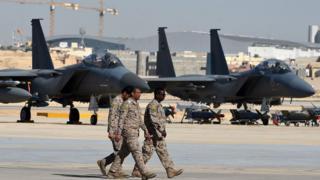 Oficiales sauditas caminan junto a cazas F-15 en una base aérea en Riad.