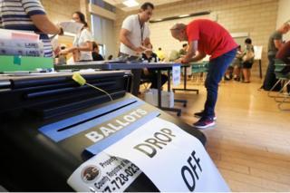 Assistentes e eleitores em sala de votação na Califórnia