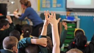 Учионица, подигнуте руке ђака