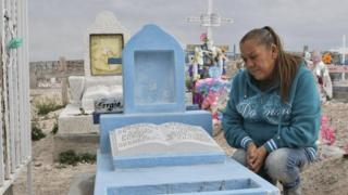 In this file photo taken on February 18, 2017 Maria Guadalupe Guereca, 60, visits the grave of her murdered son Sergio Hernandez at the Jardines del Recuerdo cemetery in Ciudad Juarez, Chihuahua, Mexico