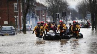 Lifeboat volunteers pull a dinghy with people onboard through flooded water in a residential street