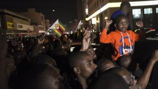HARARE, ZIMBABWE - NOVEMBER 21: Zimbabweans shout slogans and wave flags as they celebrate after the resignation of President Robert Mugabe who has ruled the country for 37 years, in Zimbabwe's capital Harare on November 21, 2017.