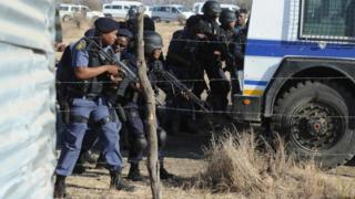 Police officers look at protesting miners near a platinum mine in Marikana on August 16, 2012