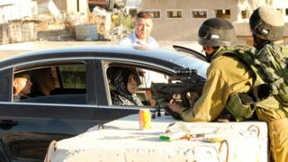 Israeli soldiers block vehicles from crossing from the West Bank city of Hebron to Yatta village on 6 July