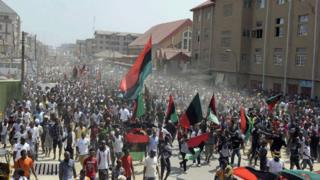 Plenty Biafra supporters dey wave flags and sing songs as dem dey march enter streets for Aba, southeastern Nigeria.