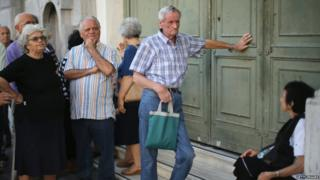 Senior citizens queue up to collect their pensions outside a National Bank of Greece branch in Kotzia Square in Athens, Greece, on Tuesday