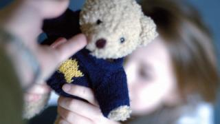 child being handed teddy
