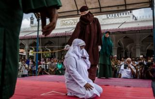 A woman on her knees is flogged in Aceh state by a hooded man