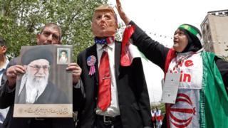 Демонстрация протеста в Иране - протестующий держит фотографию аятоллы Хаменеи, рядом фигура Трампа