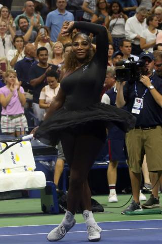 Serena Williams wearing a black tutu stood like a ballerina