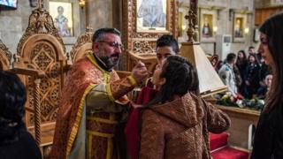 Священник дает причастие девушке