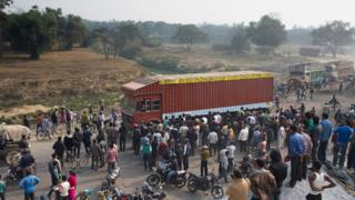 Nepalese and Indian bystanders look on as cargo trucks pass through the India-Nepal border at Birgunj, some 90kms south of Kathmandu.