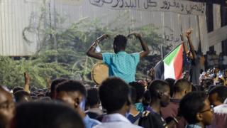 Two people sitting one others' shoulders at a sit-in at the military HQ in Khartoum, Sudan - Sunday 7 April 2019