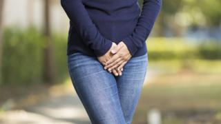 Imagem mostra mulher com as mãos cobrindo a área genital
