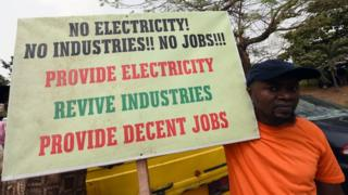 A man holds a placard reading 'No electricity! No industries!! No jobs!!! Provide electricity, revive industries, provide decent jobs' during a demonstration to protest against the 45 percent raise of electricity prices on February 8, 2016 in Lagos.