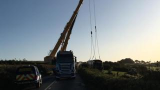 Crane lifting bus