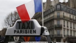 A French flag waves above a striking French taxi as drivers continue their national protest about competition from private car ride firms like Uber (27 January 2016)