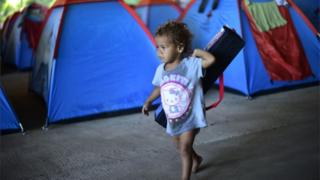 Young child walking between tents