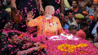 Indian Prime Minister and leader of the Bharatiya Janata Party (BJP) Narendra Modi gestures during a roadshow in Varanasi on April 25, 2019