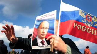 Demonstrator holding image of Putin