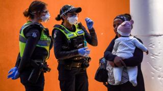 in_pictures Two police officers speak to a woman carrying a baby out the front of a locked-down housing tower