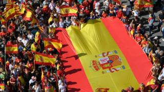 Image shows protesters holding a giant Spanish flag during a demonstration to support the unity of Spain on 8 October 2017