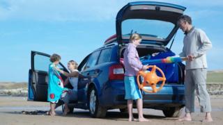 A family unpacking a car on a beach