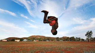 A young footballer performs a backflip during a training session in Alice Springs