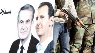 """Syrian civilians who volunteered to join local Self Protection Units to protect their neighbourhoods alongside the Syrian army attend training near a picture of Syria""""s president Bashar al-Assad and his father Hafez al-Assad, in Damascus countryside"""