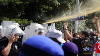 Riot police use pepper spray to push back a group of Uighur protesters who try to break through a barricade outside the Chinese Embassy in Ankara, Turkey, Thursday, June 9. 2015