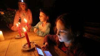 Niñas con celulares y velas