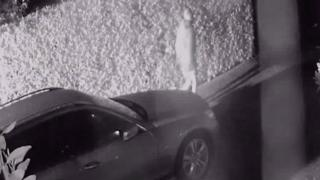 CCTV footage of a man walking past a car