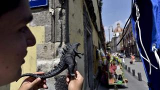 "A fan holds a Godzilla plastic toy while watching the shooting of scenes of the movie ""Godzilla, King of the Monsters"" in the historical centre of Mexico City on August 20, 2017."